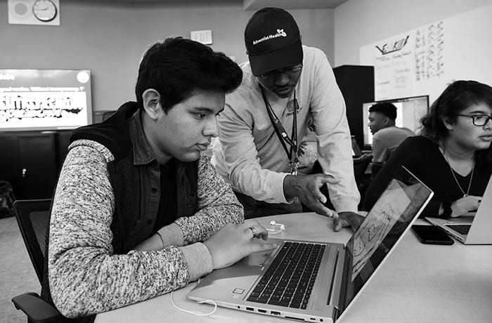 Teacher and student looking at laptop